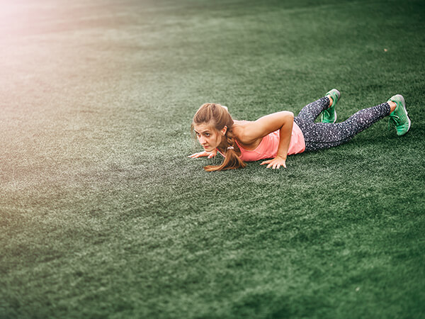 Young Woman Performing Burpee or Plank
