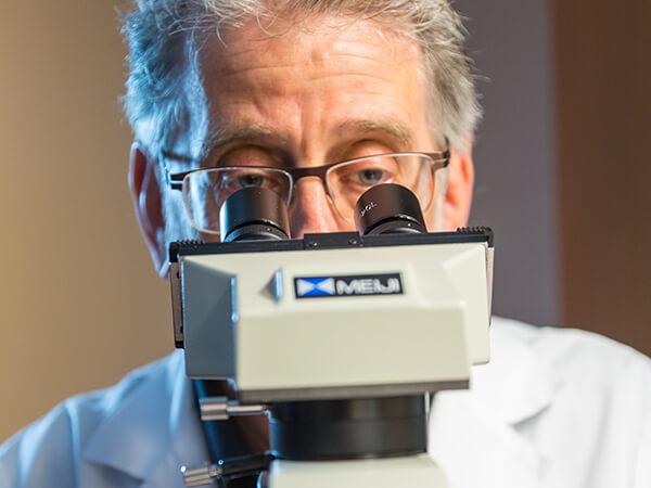 Rheumatologist Looking at Microscope